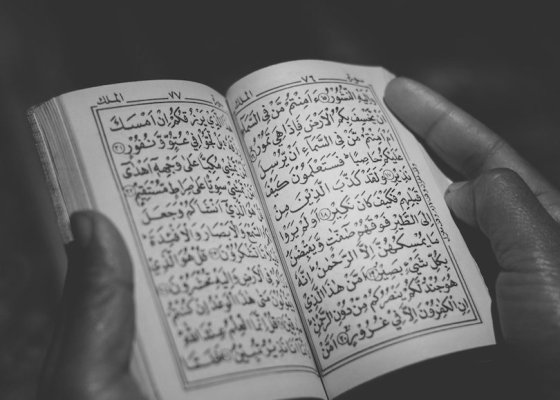 Man holding Quran black and white