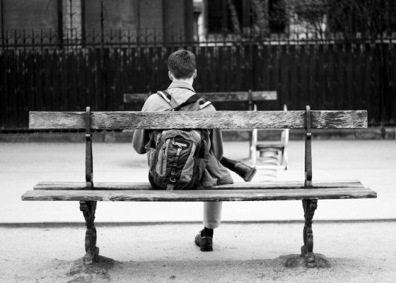 man sat on bench black and white
