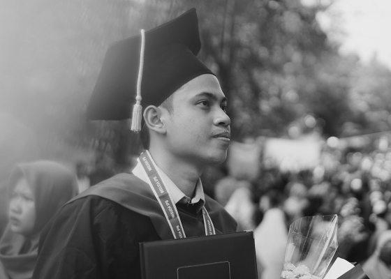 Man graduating black and white